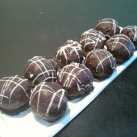 punčová zmes s ovocím, obalená v mliečnej čokoláde,postriekaná bielou čokoládou